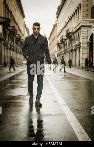 Full length of young man in coat walking under rain along the city street holding cigarette. - Stock Photo