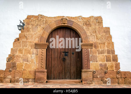 Wooden door on a colonial building with a stone arch in Barichara, Colombia - Stock Photo
