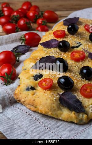 Italian bread focaccia with olive, basil and cherry tomato. Homemade traditional Italian bread focaccia on the linen - Stock Photo
