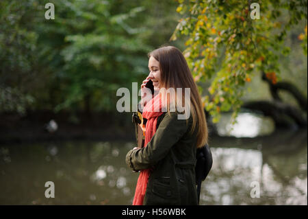 The young attractive woman walks in the autumn park. She speaks by the mobile phone and smiles. Autumn trees are - Stock Photo