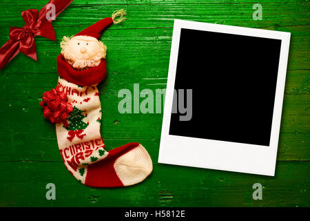 Christmas greeting postcards, sock Santa and instant empty photo frame on green wood - Stock Photo