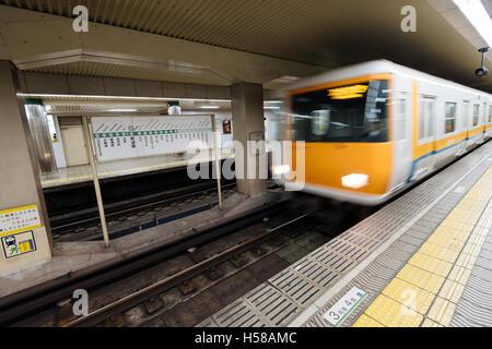Osaka, Japan - November 30, 2015: Osaka subway station and motion blurred train. - Stock Photo