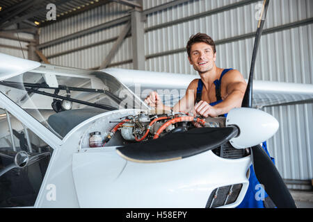 Cheerful young air mechanic standing and working with small plane - Stock Photo