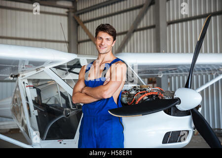Happy attractive young aircraft mechanic standing with arms crossed near small airplane - Stock Photo