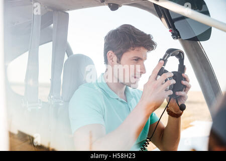 Handsome young man pilot in cabin of small aircraft - Stock Photo
