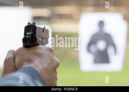 Man Firing Pistol at Target in Shooting Range - Stock Photo