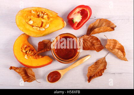Pumpkin sauce or ketchup in glass jar, raw pumpkin and autumnal leaves on wooden table, healthy nutrition - Stock Photo