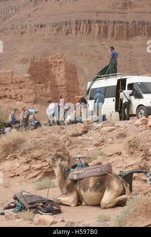Local guides unload supplies from a minibus in the mountains of Southern Morocco at the start of a Sahara desert - Stock Photo