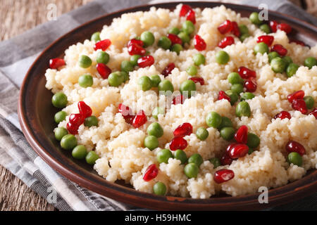couscous with green peas and pomegranate close-up on the table. Horizontal - Stock Photo