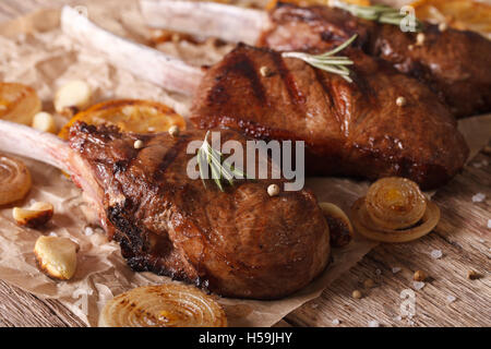 Rustic grilled beef steak with rosemary on a paper on the table close-up. Horizontal - Stock Photo