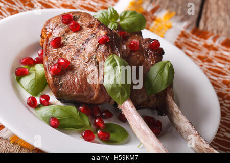 beef steak with pomegranate seeds and basil close-up on a plate. Horizontal - Stock Photo