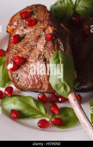 beef steak with pomegranate seeds and basil macro on a plate. vertical - Stock Photo