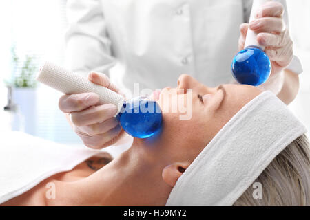 Wave roller massage. Cosmetic treatment, facial massage glass balls - Stock Photo