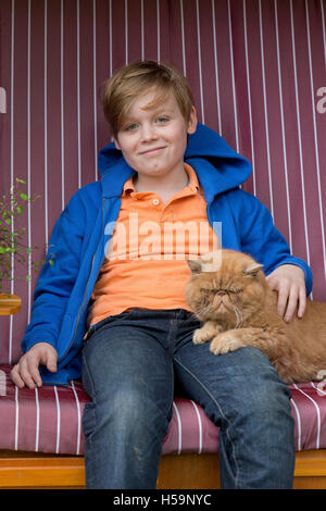 young boy caressing cat at children´s farm Kirchdorf, Hamburg, Germany - Stock Photo