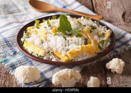 Dietary food: cauliflower rice with scrambled eggs and herbs closeup on a plate. horizontal - Stock Photo