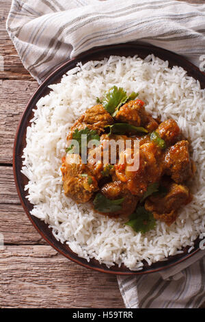 Indian food: Madras beef with basmati rice on the table close-up. vertical view from above - Stock Photo