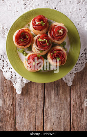 Baked rolls with salami in the form of roses on the table. Vertical top view - Stock Photo