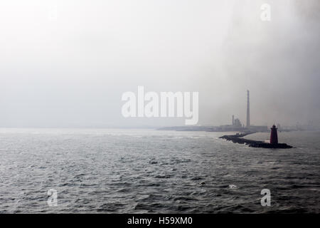 Industrial landscape showing a lighthouse and smoking chimneys,pollution rising into the atmosphere,Dublin,Ireland. - Stock Photo