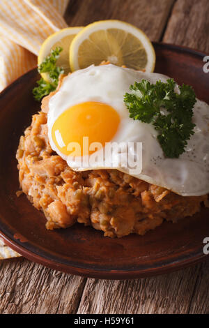 Arabic cuisine: ful medames with a fried egg on a plate close-up. vertical - Stock Photo
