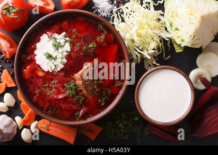Ukrainian food: red soup borsch with ingredients on slate board closeup. Horizontal view from above - Stock Photo
