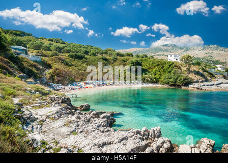 Kassiopi Beach, Corfu Island, Greece. Sunbeds and parasols (sun umbrella) on the beach. Tourists relaxing on the - Stock Photo