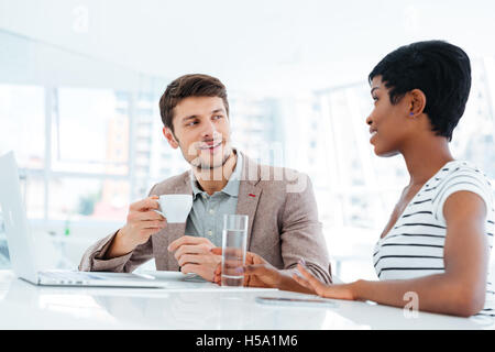 Young man and woman sitting and working with laptop together in office - Stock Photo