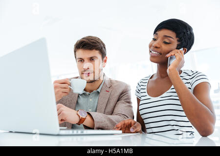 Cheerful beautiful african business woman talking on cell phone and working with serious man in office - Stock Photo