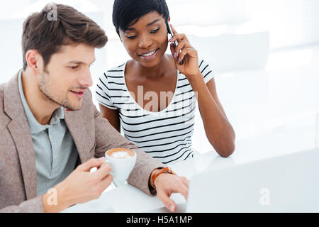 Happy young business man and woman sitting and working together in office - Stock Photo