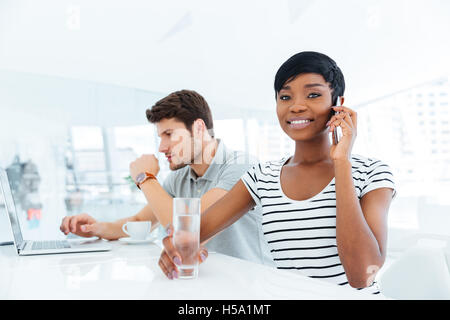 Young businesswoman and businessman working together in office with laptop - Stock Photo