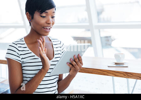 Happy afro american businesswoman holding tablet computer and waving in office - Stock Photo