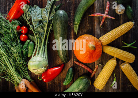 High angle view of various fresh vegetables on wooden table - Stock Photo