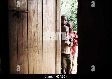group of African children stare through a doorway at the westerner in their home - Stock Photo