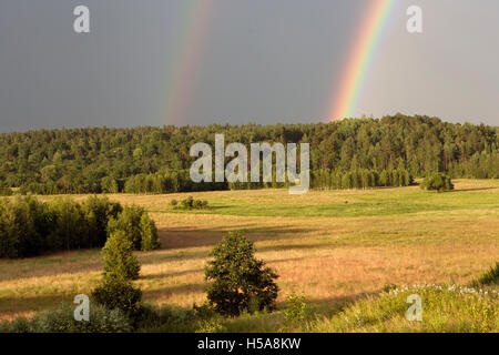 Bright primary and secondary rainbows over Gaujiena Valley in Latvia - Stock Photo