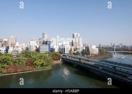 Osaka, Japan - November 30, 2015: Kyū-Yodo River  and  skyscrapers of downtown Osaka, Japan. Osaka is a large port - Stock Photo