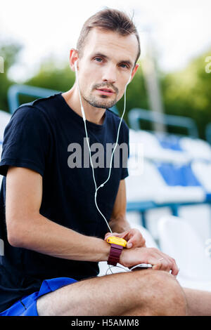 Athletic man in sportswear and white headphones touching his wristwatch - Stock Photo