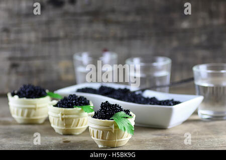 black caviar on a wooden background - Stock Photo