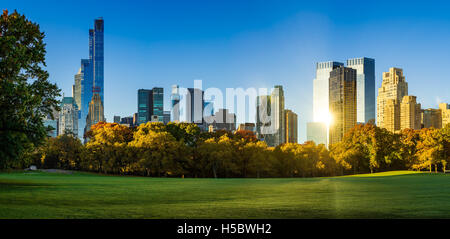 Central Park Sheep Meadow in full autumn colors. Midtown Manhattan skyscrapers in early morning light. New York - Stock Photo