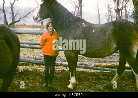 A little girl standing next to a horse, 1970 - Stock Photo