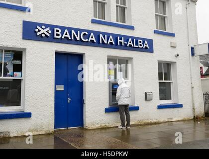 A man withdrawing money from cash machine at Bank of Scotland bearing the name in Gaelic on the Isle of Skye, Scotland, - Stock Photo