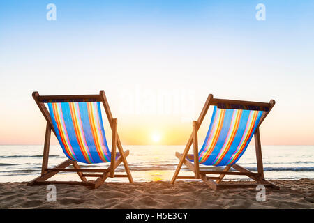 Two deck chairs on a tropical sandy beach with beautiful colorful sunset - Stock Photo