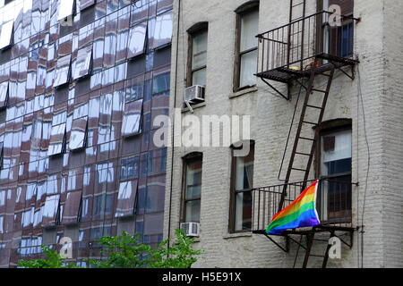 Gay pride flag (rainbow flag) hanging on the fire escape of an old apartment building, Chelsea, New York City, NY, - Stock Photo