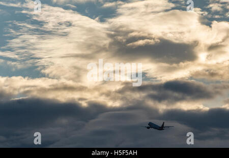 Berlin, Germany. 20th Oct, 2016. A plane flying past dark clouds towards the sun at Tegel airport in Berlin, Germany, - Stock Photo