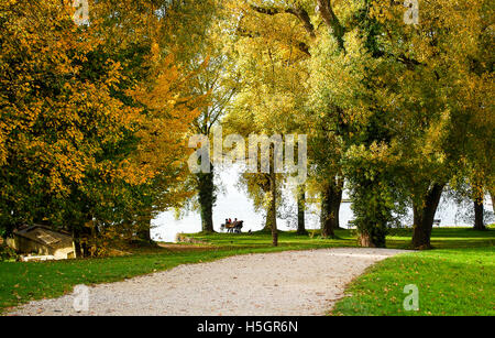 People enjoying a warm autumn afternoon at Lake Chiemsee in Germany - Stock Photo