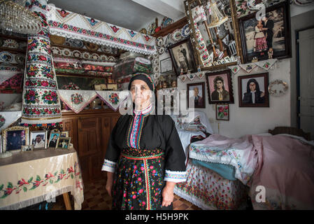 Traditional Greek house and local woman Olympos Village Karpathos Island Greece - Stock Photo