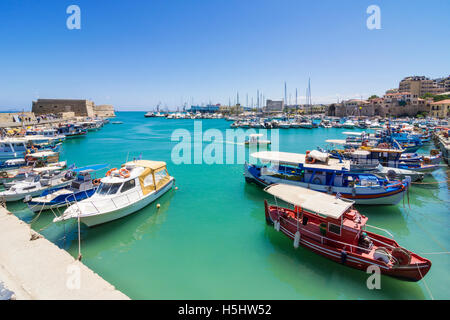 Fishing boats moored in old Venetian harbour next to the Koules Fortress, Heraklion, Crete, Greece - Stock Photo