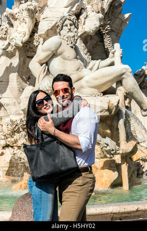 Tourist couple embrace in front of Fountain of the four Rivers in Piazza Navona, Rome, Lazio, Italy - Stock Photo