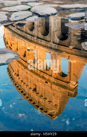 Colosseum or Coliseum reflected in a puddle at sunset, Rome, Lazio, Italy - Stock Photo