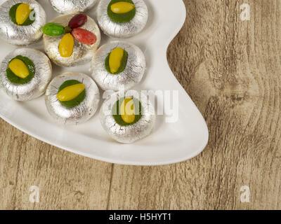 kaju kalash kaju badam and pista sugar virk served in a white plate on wooden background - Stock Photo