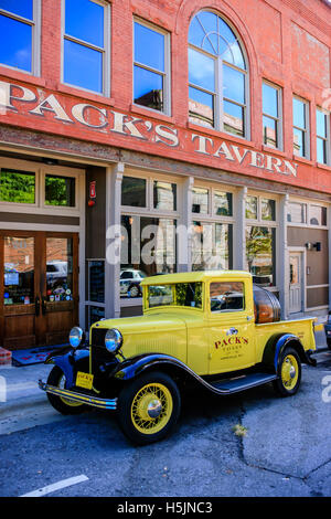 A 1930s yellow pickup truck outside Pack's Tavern on Spruce Street in downtown Asheville NC - Stock Photo