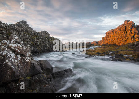Morning light catches a cliff over a river in Thingvellir National Park, Iceland. - Stock Photo